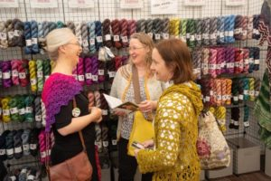 knitters in front of yarn vendor booth talking and smiling at woollinn yarn festival
