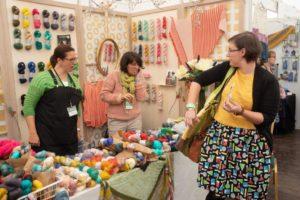 knitters browsing yarn vendor booth at woollinn yarn festival