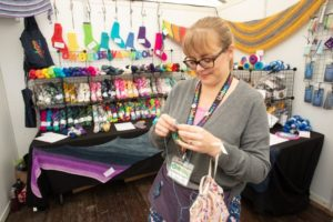 knitter working on knitting project in front of vendor booth at woollinn yarn festival