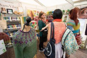 knitters browsing colourful booth of yarn at woollinn yarn festival