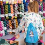 knitter browsing wall of colourful yarn at woollinn yarn festival
