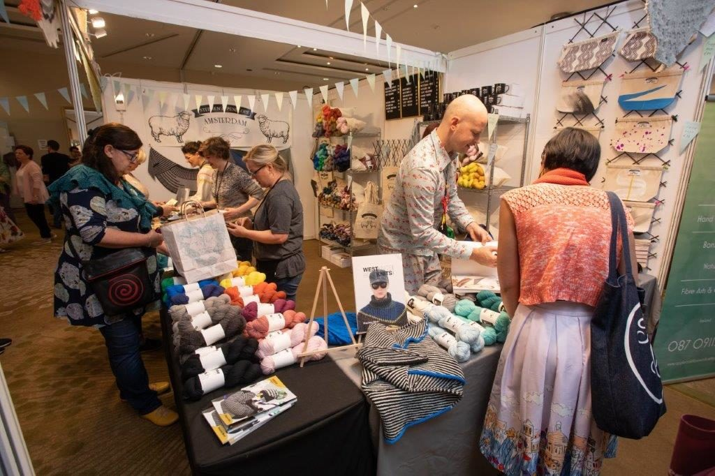 knitters shopping for yarn at vendor booth at woollinn yarn festival