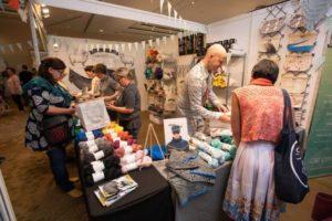 knitters shopping for yarn at vendor booth at woollinn yarn festival