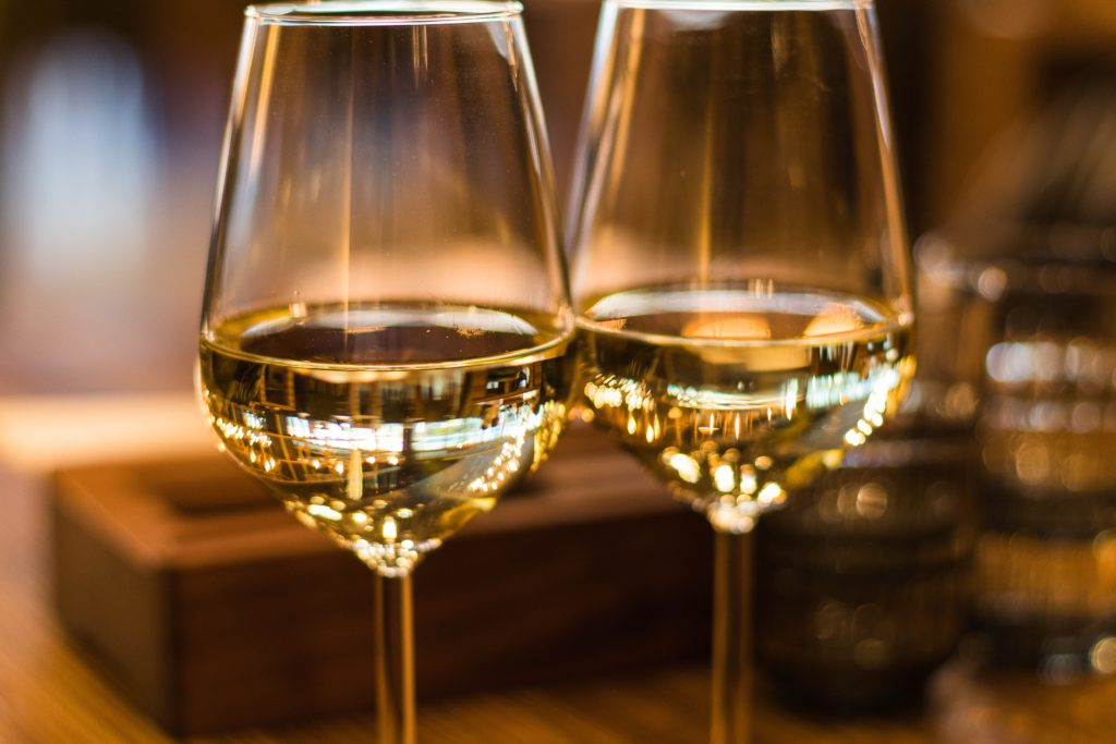 close up of two glasses of white wine sitting next to each other