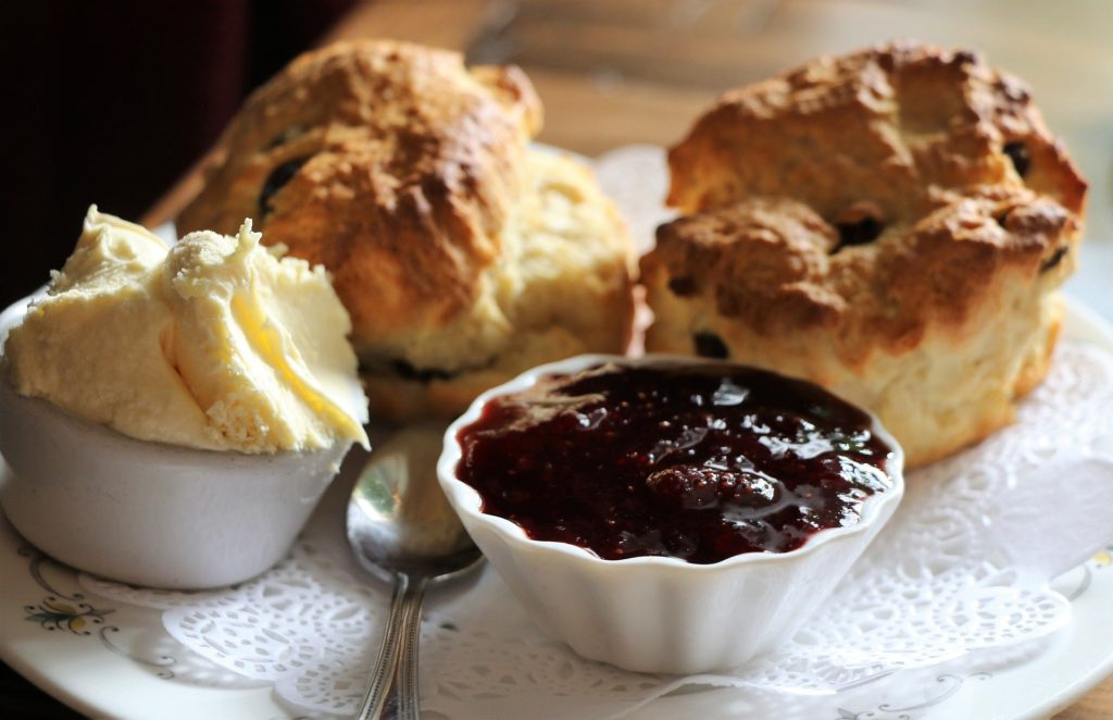 plate of scones with ramekins of jam and cream